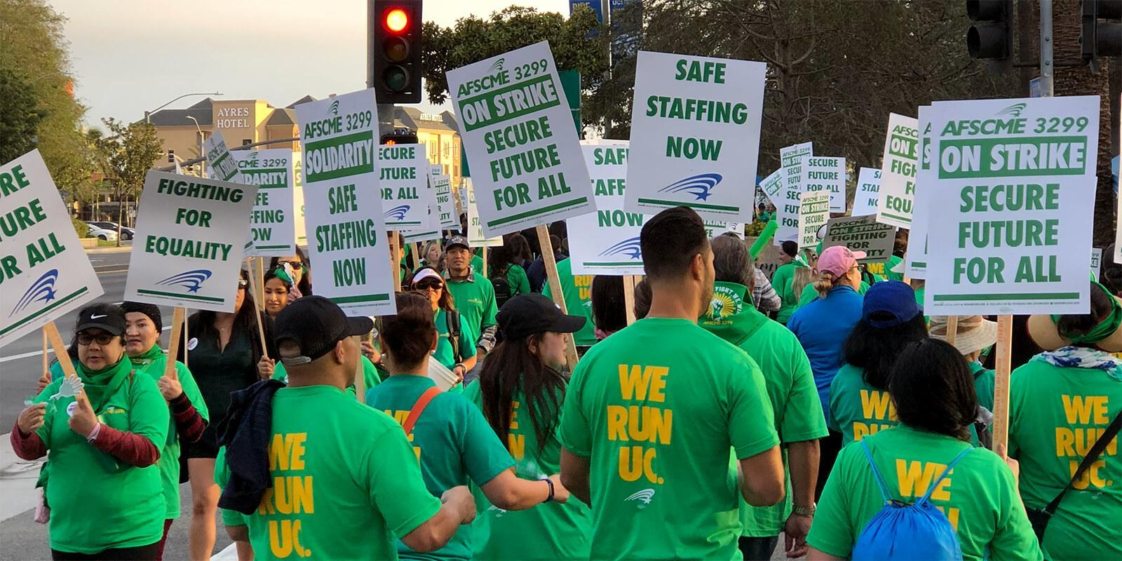 "AFSCME 3299 members on the picket line with signs that read, ""On Strike, Secure Future For All"" and ""Safe Staffing Now"""